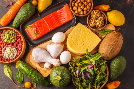 Foto de Keto diet concept. Balanced low-carb food background. Vegetables, fish, meat, cheese, nuts on a dark background. - Imagen libre de derechos