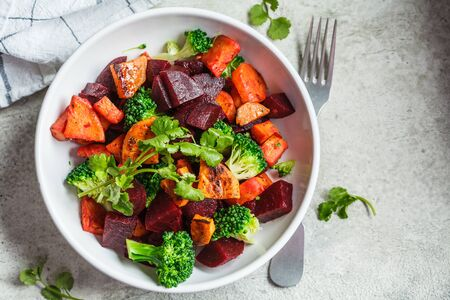 Photo for Baked sweet potato, beetroot and broccoli salad in a white bowl. - Royalty Free Image
