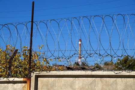Photo for Barbed wire on the concrete fence protecting the industrial enterprise - Royalty Free Image