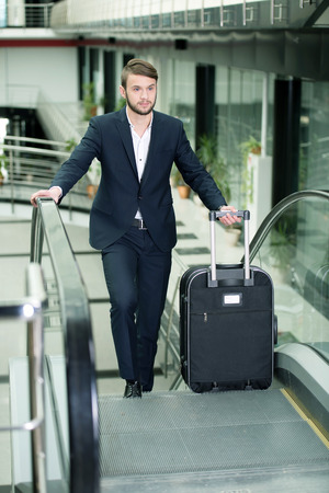 Young businessman with a suitcase and plane tickets at the airport to travel trips
