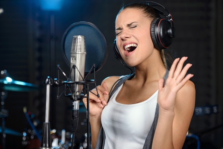 Photo for Portrait of young woman recording a song in a professional studio - Royalty Free Image