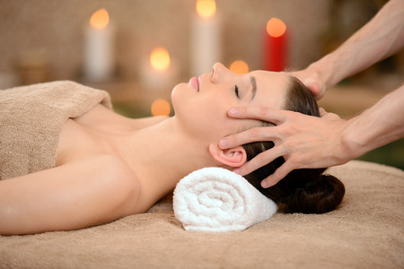 Photo pour Portrait of Fresh and Beautiful brunette woman taking head massage isolated on background spa salon - image libre de droit