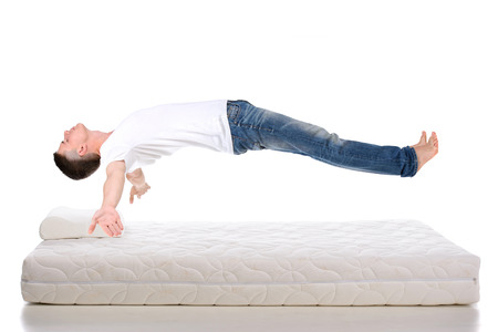 Photo pour Orthopedic mattress. A young man sleeping on a mattress, side view. Flying during sleep Isolated on white background - image libre de droit