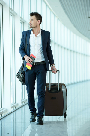 Foto de Business traveler pulling suitcase and holding passport and airline ticket - Imagen libre de derechos