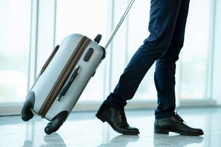 Photo pour Business traveler pulling suitcase and holding passport and airline ticket - image libre de droit