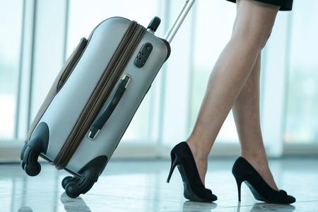 Photo pour Business woman traveling with trolley. Women's legs, close-up - image libre de droit