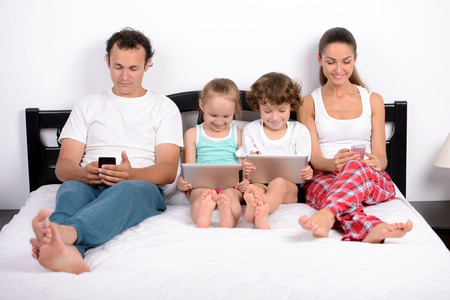 Photo pour Modern technology in home. Young family, the use of tablets and phones, lying in bed at home - image libre de droit