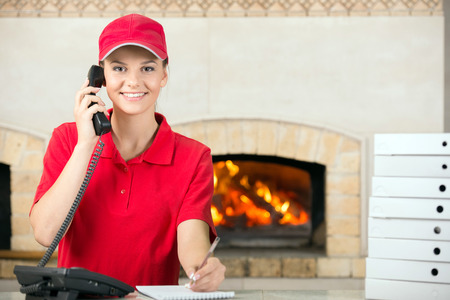 Photo for Smiling delivery woman of pizza holding pen and diary for placing order by phone. - Royalty Free Image