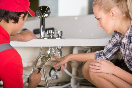 Foto de Professional plumber. Plumbing repair service. Woman is showing damage plumbing. - Imagen libre de derechos