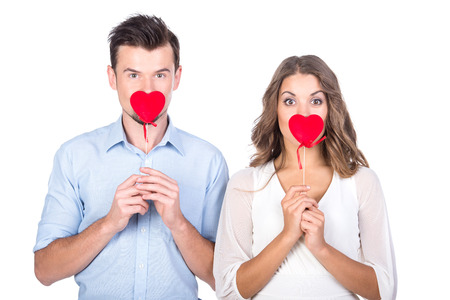 Photo pour Loving couple. Beautiful young loving couple holding paper hearts and smiling while isolated on white - image libre de droit