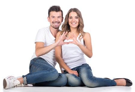 Photo pour Valentine couple. Portrait of smiling beauty girl and her handsome boyfriend making shape of heart by their hands. Happy joyful family. Love concept. Heart sign. Laughing happy lovers. Valentines Day - image libre de droit