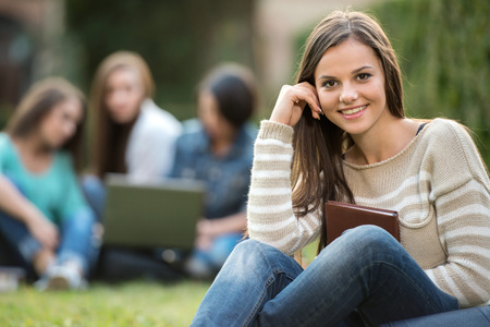 Portrait of a beautiful, smiling college girl is holding book with blurred students are sitting in the park.