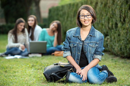 Portrait of a young, asian, smiling female student, with blurred students are sitting in the park. She is looking at the camera.