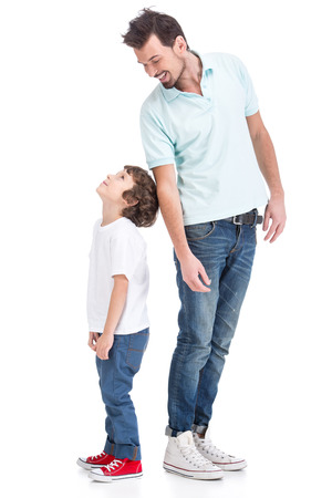 Photo for Portrait of happy father and his little son, on the white background. They are looking at each other. - Royalty Free Image