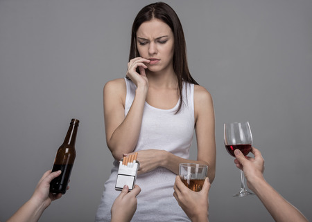 Foto de Portrait of a young woman who refuses to alcohol and tobacco. Young girl struggling with her bad habits. - Imagen libre de derechos