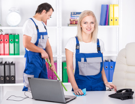 Photo pour Young couple professional cleaners are cleaning the office. - image libre de droit