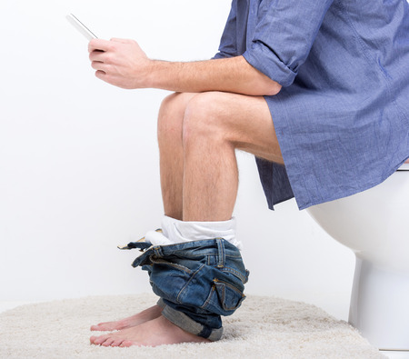 Businessman is working with digital tablet while sitting on the toilet.