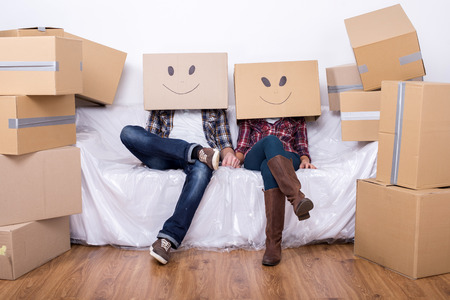 Foto de Couple with cardboard boxes on their heads with smiley face are sitting on floor after the moving house. - Imagen libre de derechos