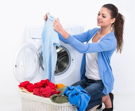 Foto de Happy young woman is doing laundry with washing machine at home. - Imagen libre de derechos