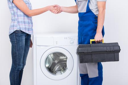 Foto per Handshake of housewife and repairman near the washing machine. - Immagine Royalty Free