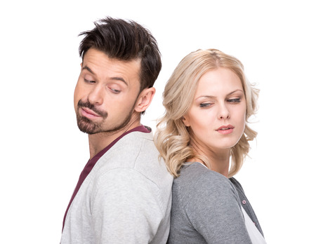 Photo pour Unhappy young man and woman are standing back each other and not speaking, isolated on white background. - image libre de droit