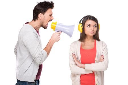 Foto de Young man shouts at the woman in a megaphone. Woman with headphones while he screams.  - Imagen libre de derechos