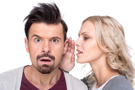 Photo for Amazed man is listening gossip in the ear from woman, on the white background. - Royalty Free Image