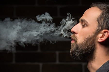 Foto de Side view of young bearded man is smoking against brick wall. - Imagen libre de derechos