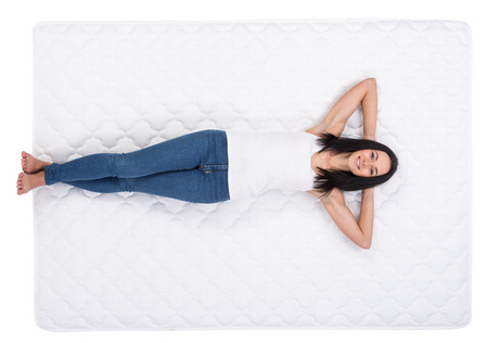 Foto de Young woman is lying on the bed. Quality mattress. - Imagen libre de derechos