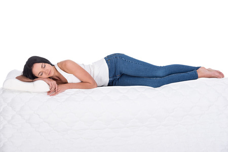 Foto de Young woman is lying on the mattress. Isolated on white background. Side view. - Imagen libre de derechos