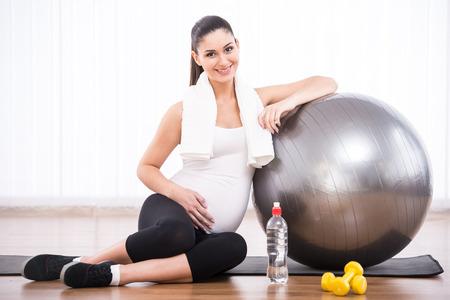 Photo pour Pregnant woman is doing exercises with gymnastic ball. - image libre de droit