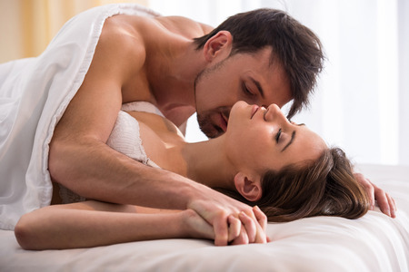 Photo for Young love couple in bed, romantic scene in bedroom. - Royalty Free Image