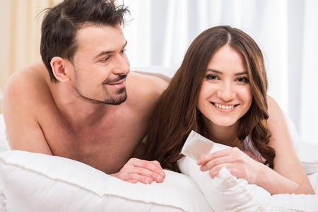 Foto de Young attractive couple in bed with a condom. - Imagen libre de derechos