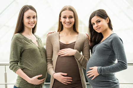 Photo pour Maternity concept. Portrait of three happy pregnant women. - image libre de droit