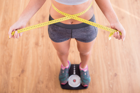 Foto de Top view of pretty slim woman with measure around her body is standing on the scales. - Imagen libre de derechos