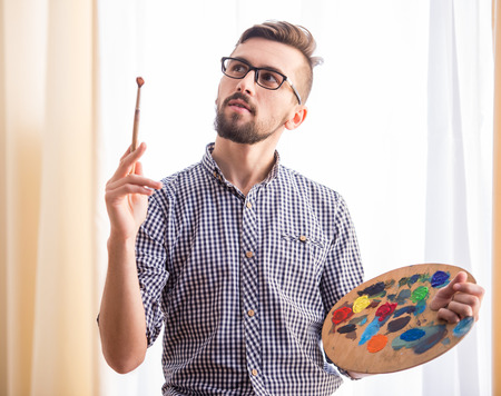 Photo for Portrait of a young male artist is holding a brush and mix color oil painting on palette. - Royalty Free Image