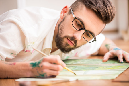 Photo for Young artist is painting on canvas is lying on studio floor. Close-up. - Royalty Free Image