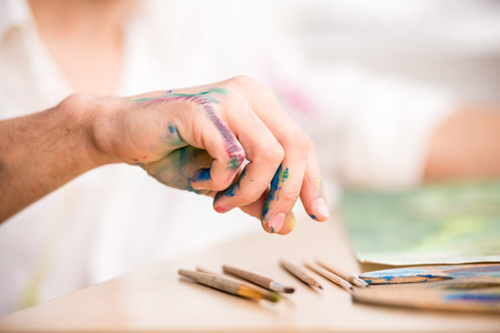 Photo for Close-up hand of young artist with brushes while is painting his picture. - Royalty Free Image