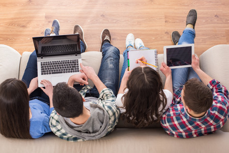 Photo pour Top view of a four young people, students are sitting on sofa with laptop and tablet, are studying. - image libre de droit
