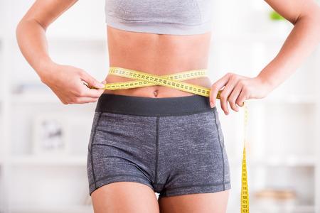 Foto de Sporty woman and measure around her body at home. - Imagen libre de derechos