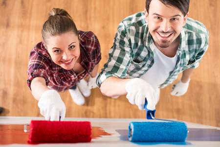 Foto de Top view of young couple are doing repair at home and painting a wall with roller. - Imagen libre de derechos