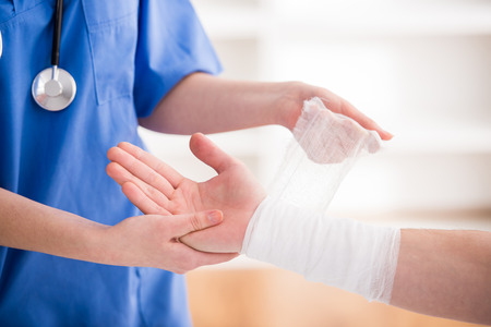 Photo pour Close-up female doctor is bandaging upper limb of patient. - image libre de droit