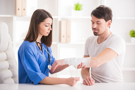 Photo pour Pretty female doctor is bandaging upper limb of young man. - image libre de droit