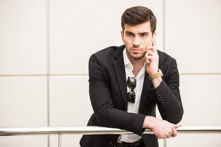 Foto de Portrait of young trendy man is talking by phone. - Imagen libre de derechos