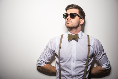 Foto de Portrait of young trendy man with black glasses, suspenders and bow-tie on gray background. - Imagen libre de derechos
