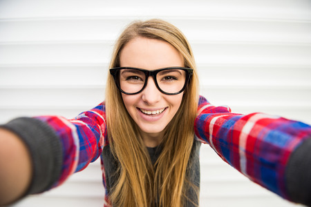 Photo pour Close-up of trendy girl face in sunglasses is making selfie photo. - image libre de droit