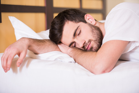 Photo pour Close-up of young man is sleeping on bed. - image libre de droit