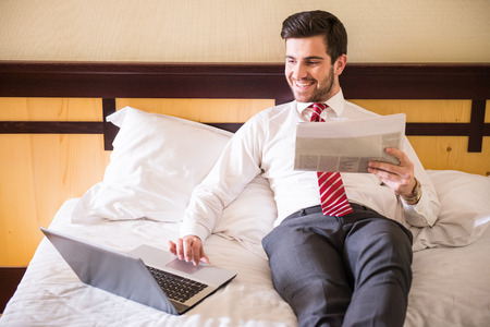 Photo for Handsome businessman is working with laptop, sitting on the bed in hotel room. - Royalty Free Image