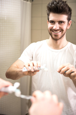 Photo for Dental health care clinic. Young man is holding a toothbrush and placing toothpaste on it. - Royalty Free Image