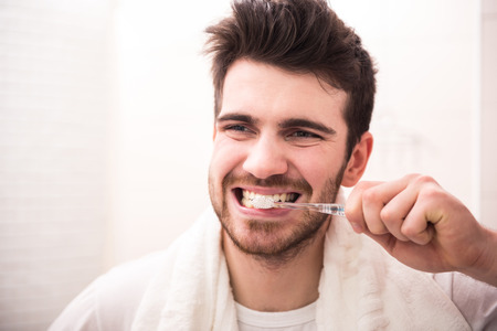 Photo pour Morning routine of washing the teeth. Handsome young man is brushing teeth with toothbrush. - image libre de droit
